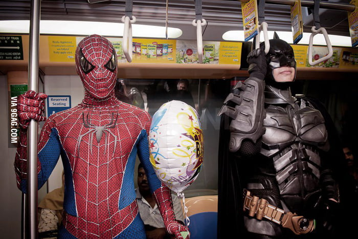 Spiderman and Batman riding the subway