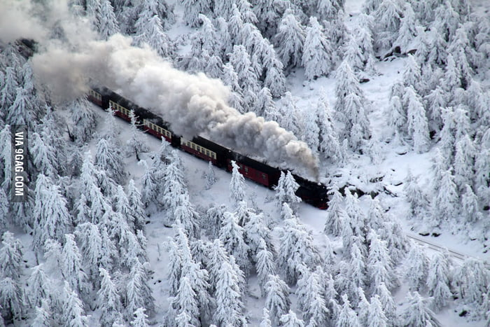 Smoky train going through snowy woods in Germany.