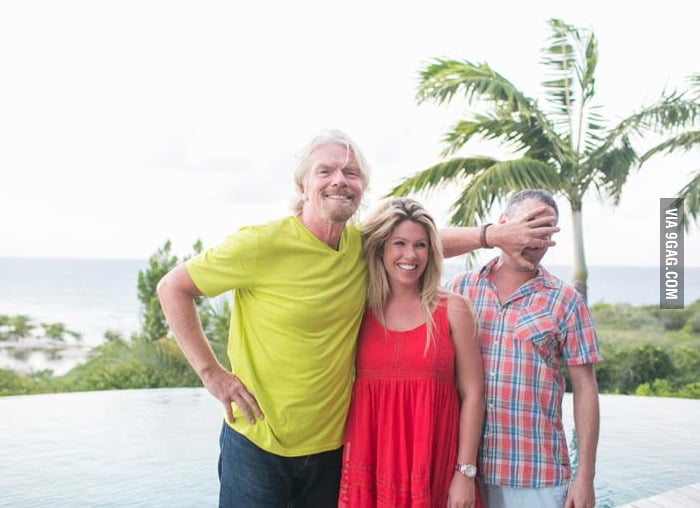 A couple taking a picture with Sir Richard Branson.