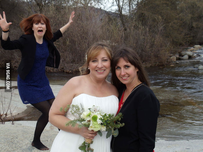 She lost her balance while trying to photobomb at a wedding.