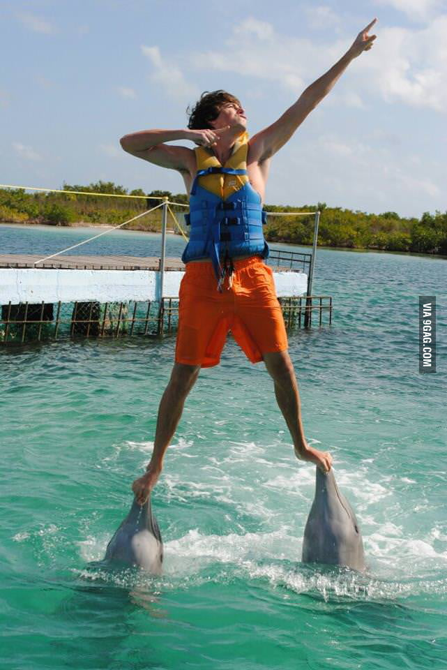 Standing on dolphins' mouths and doing the Usain Bolt sign.