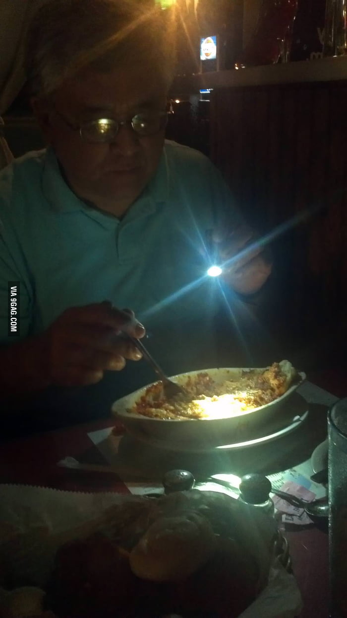 The restaurnat is so dark that a torch is needed.