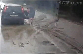 Dad holding child almost nailed by a car.