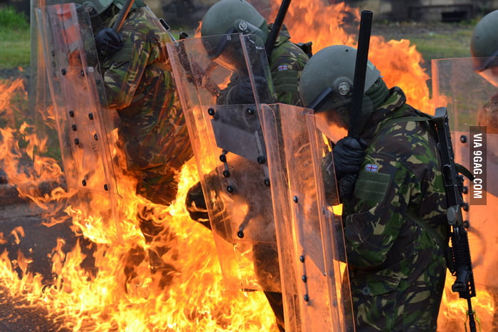 Salute! British riot troops stand firm against petrol bombs.