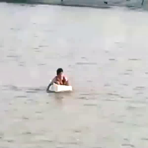 An elementary school student in indonesia goes to school by sailing on a styrofoam box