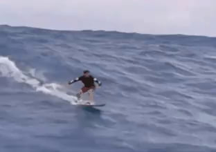 Surfer beats a huge wave like it's easy .