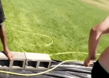Guy attempts to slip-n-slide down a hill STANDING UP