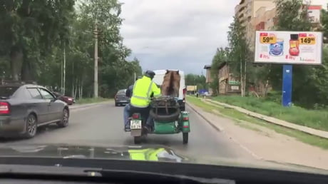 Just a bear riding in a motorcycle sidecar waving to people