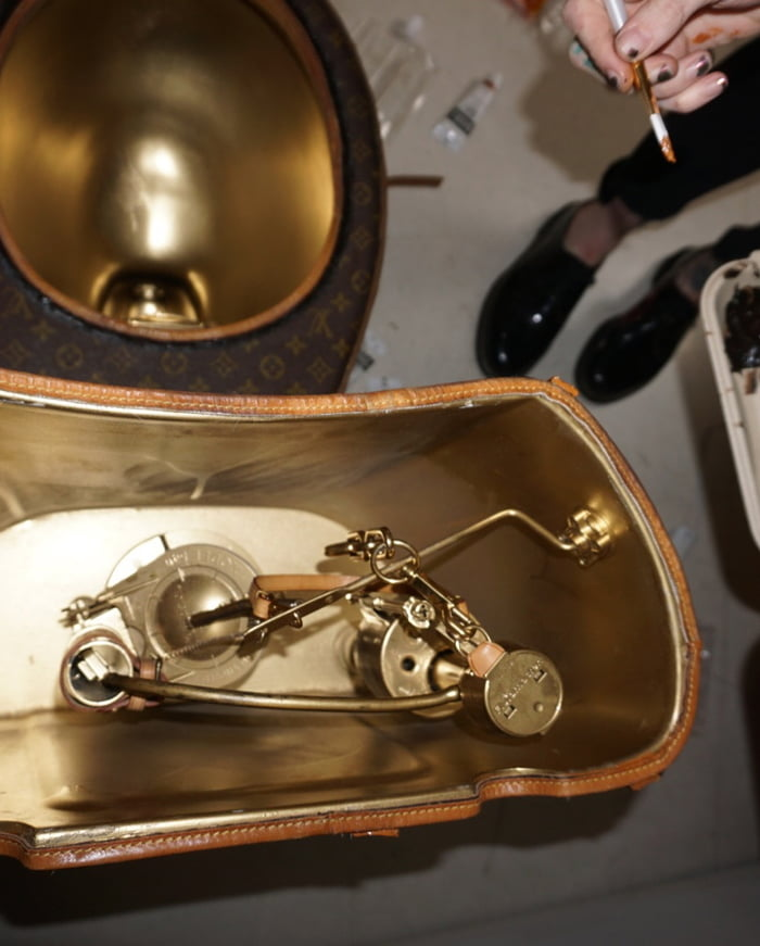 gold plated toilet seat.  creating it from designer bags valued at USD 15 000 in total including a 3 suitcase A fully functioning golden toilet the iconic Louis Vuitton Toilet Is Now Available And It Made With 24 LV