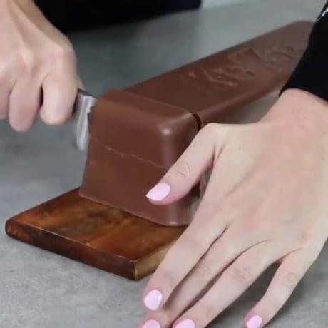 Cutting into a giant Kit Kat bar